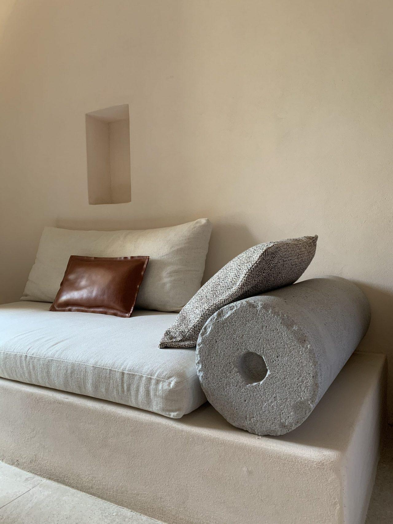 divano in cemento e cuscini in tessuto e cuoio